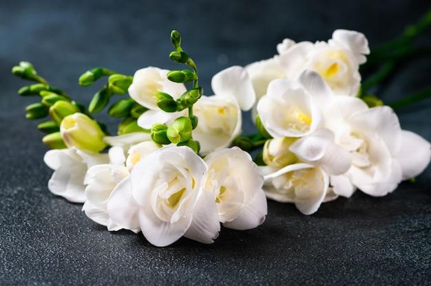暗い表面に花とつぼみがある白いフリージアの枝。テーブルの上の花。フリージアの花。