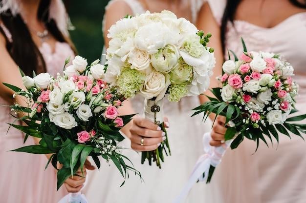 Невеста и подружки невесты в элегантном платье стоят и держат в руках букеты пастельно-розовых цветов и зелени с лентой на природе. молодые красивые девушки держат свадебный букет на открытом воздухе.