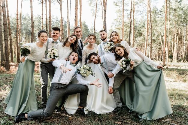 신랑 신부와 친구들이 즐겁고 포옹하고 있습니다.