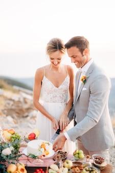 신부와 신랑이 산에서 결혼식 후 뷔페 테이블에서 케이크를 자르고 있습니다.