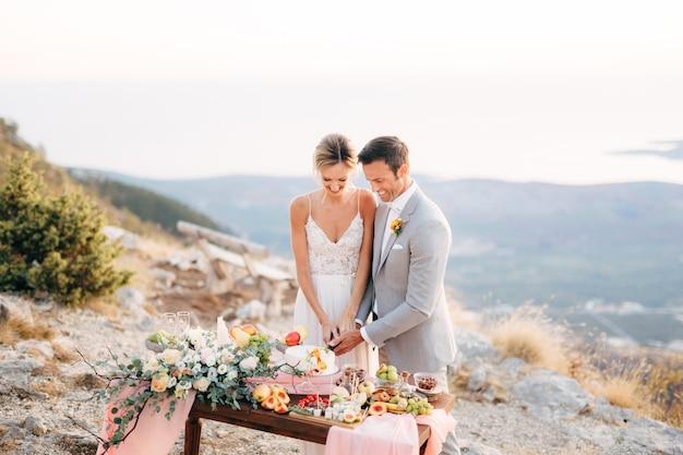 신부와 신랑이 결혼식 후 뷔페 테이블에서 케이크를 자르고 있습니다.