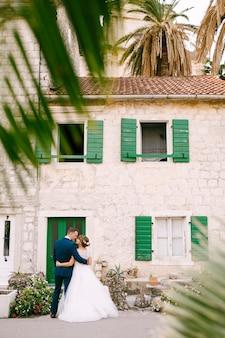Жених и невеста обнимаются перед красивым белым домом с зелеными дверями и ставнями.