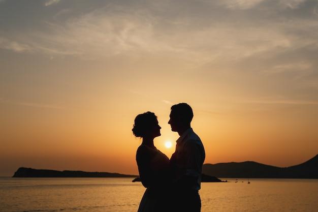 신부와 신랑이 해질녘 해변에서 포옹하고 서로를 바라보고 있습니다.