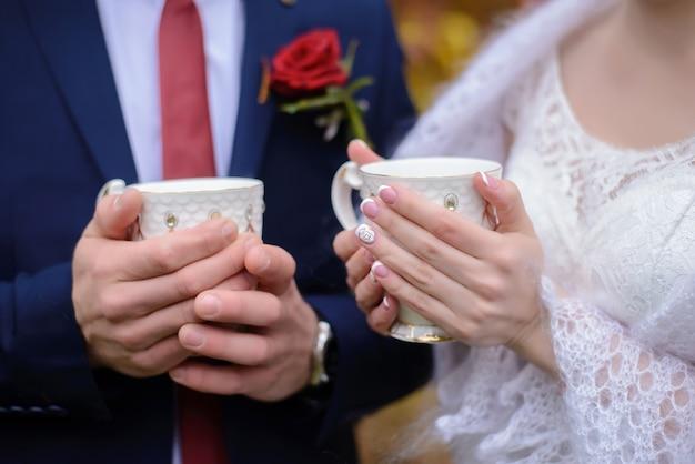 Жених и невеста держат кружки чая