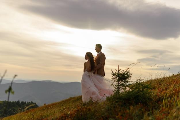 新郎新婦は日没で抱いています。フレームには明るい太陽が輝いています。日没。秋の山を背景に結婚式の写真。強い風が髪と服を膨らませます。