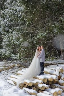 Жених и невеста обнимаются на фоне снежного елового леса. идет снег. зимняя свадьба.