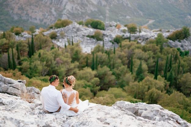 Жених и невеста сидят, обнимаясь, на скале на горе ловчен и смотрят друг на друга.
