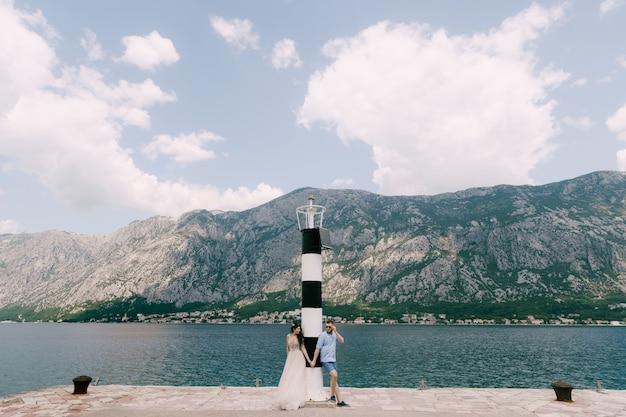 Жених и невеста стоят и держатся за руки на пристани возле маяка в бухте