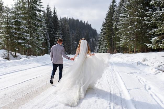 Жених и невеста гуляют за руку на фоне зимнего леса. идет снег. пара обернулась.