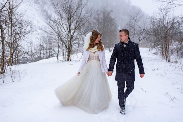 Жених и невеста гуляют за руку на фоне зимнего леса. идет снег.