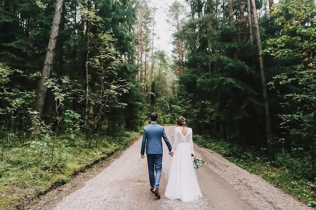 Жених и невеста гуляют в парке на природе