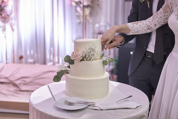 宴会の新郎新婦は、一本のナイフを持ってウエディングケーキを一緒に切りました。結婚式の詳細のクローズアップ
