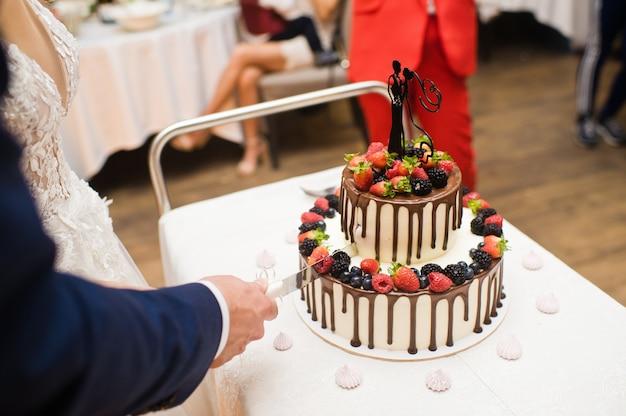 신부와 신랑은 초콜릿 웨딩 케이크를 잘라.