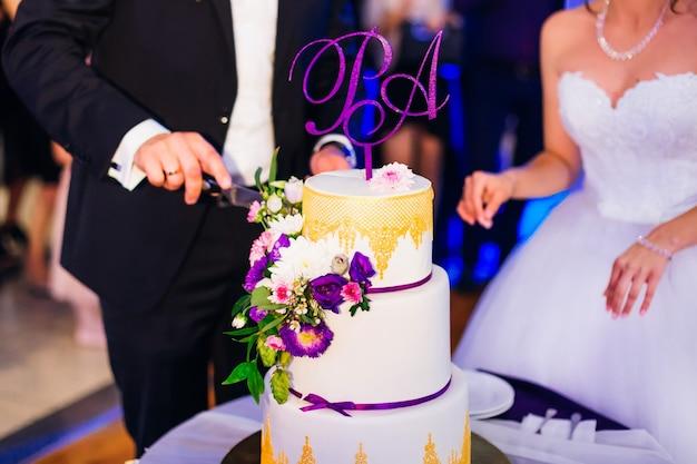 신부와 신랑이 웨딩 케이크를 자릅니다. 레스토랑.