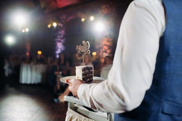 新郎新婦はウエディングケーキを切りました。カットと目に見えるフィリングの美しいケーキ。愛という言葉のウエディングケーキ、結婚式のコンセプト