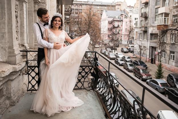 신부와 신랑이 발코니에서 포옹합니다. 커플 발코니에서 포옹하고 인생을 즐기십시오
