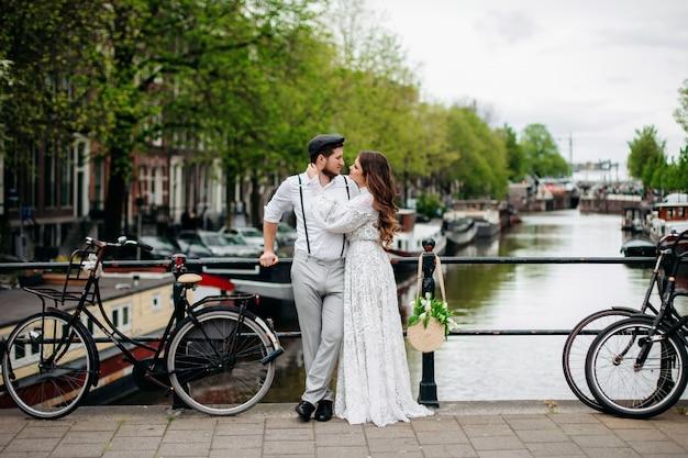 Жених и невеста обнимаются на мосту рядом с велосипедом. стилизованная ретро-свадьба.