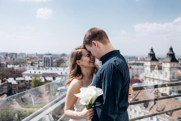 Жених и невеста, охватывающих и стоящих на балконе