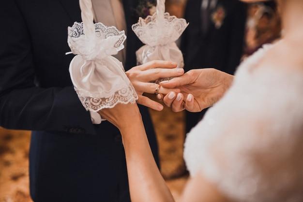 Жених и невеста обмениваются кольцами. мужчина надевает обручальное кольцо на руку женщины