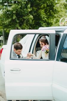 Жених и невеста выходят из лимузина. жених помогает невесте выйти из машины