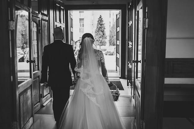 Жених и невеста спускаются по старой лестнице, выходят из церкви после венчания. вид сзади. молодожены. черно-белое фото.