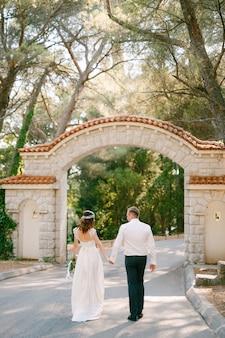 Жених и невеста идут к красивой арке у входа в парк, держась за руки, вид сзади. видео высокого качества в формате fullhd