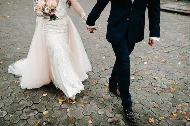 Жених и невеста идут впереди по тротуару и гуляют