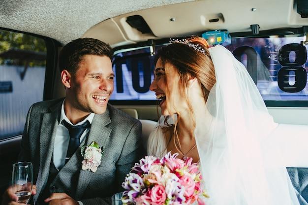 Жених и невеста развлекаются в лимузине