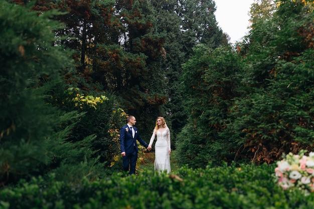 Жених и невеста держатся за руки и смотрят друг на друга гуляют в парке