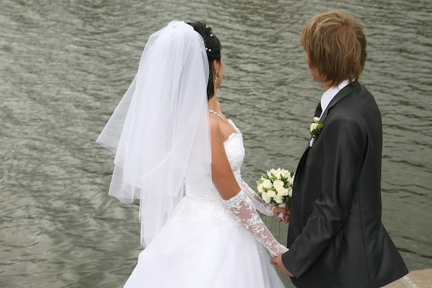 신랑 신부가 손을 잡고 물을 바라본다.