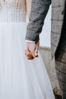 Жених и невеста держатся за руки. пара вместе мужчина и женщина в день свадьбы
