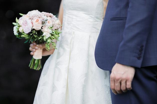 Жених и невеста держат свадебный букет