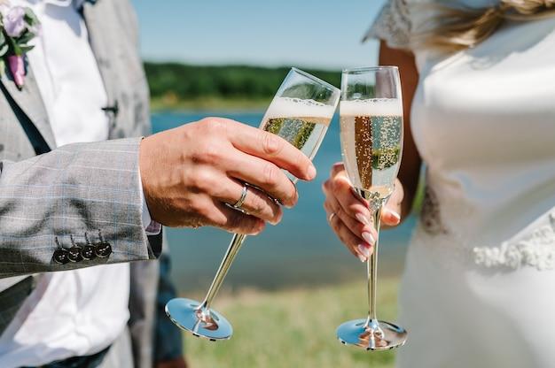 Жених и невеста держат бокал шампанского и стоят на природе во время свадебной церемонии. закройте вверх. праздничный день. посмотри на очки. тост.