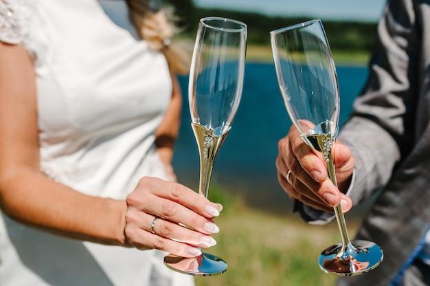 Жених и невеста держат бокал шампанского и стоят на природе во время свадебной церемонии. закройте вверх. праздничный день. тост.