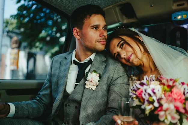 Жених и невеста обнимаются в лимузине. невеста лежит на плече жениха