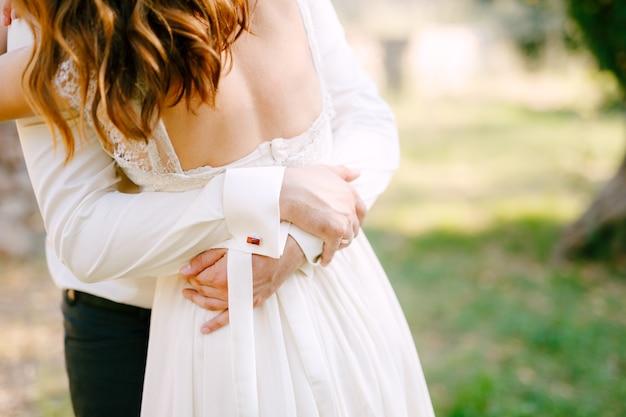 Жених и невеста обнимаются в парке, жених кладет руки на спину невесты. фото высокого качества