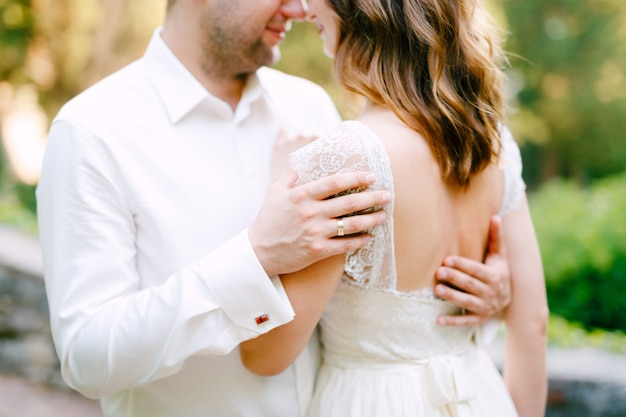Жених и невеста обнимаются в парке, жених кладет руки на спину невесты
