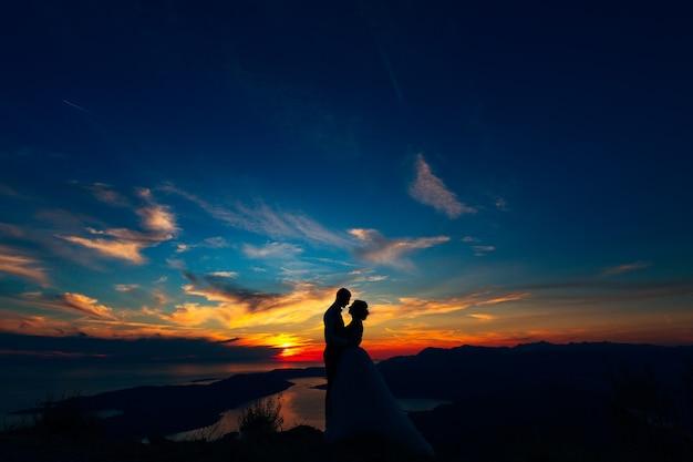 석양에 의해 코 토르만이 내려다 보이는 lovcen 산 꼭대기에서 포옹하는 신부와 신랑