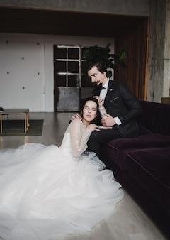 ソファの上のホテルの新郎新婦。スーツを着たスタイリッシュな男と美しい妻