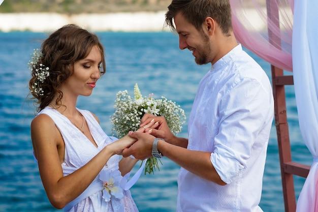 Жених и невеста в белых одеждах с букетом белых цветов стоят под аркой из цветов и ткани на фоне голубого озера и белого песка и надевают друг другу обручальное кольцо