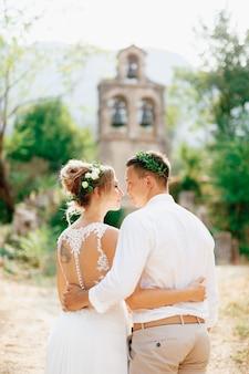 Prcanjの教会の近くの古代の鐘楼で抱き締める花輪の新郎新婦