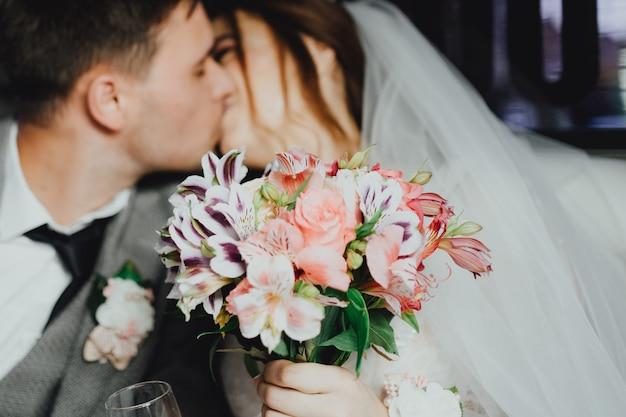 Жених и невеста целуются в лимузине