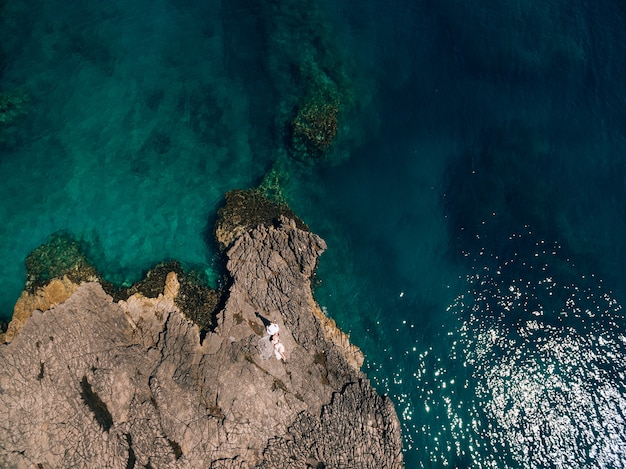 Жених и невеста лежат бок о бок на каменистом берегу и смотрят друг на друга вид сверху