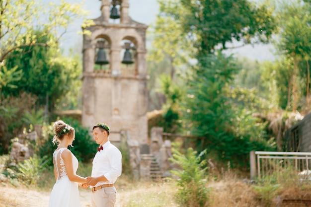 Жених и невеста смотрят друг на друга, держатся за руки и целуются у древней колокольни рядом