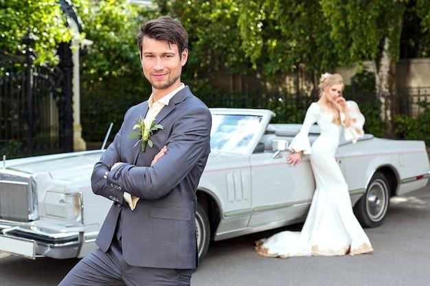 Жених и невеста возле ретро-автомобиля. свадьба. портрет жениха крупным планом