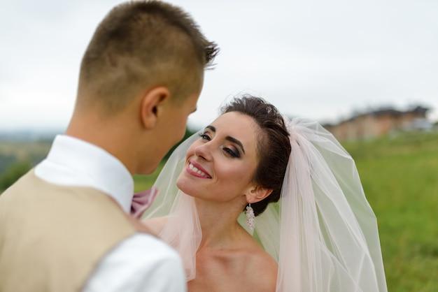 結婚式の散歩に新郎新婦。愛するカップルが抱擁し、お互いの目を見つめます。花嫁に焦点を当てます。閉じる。