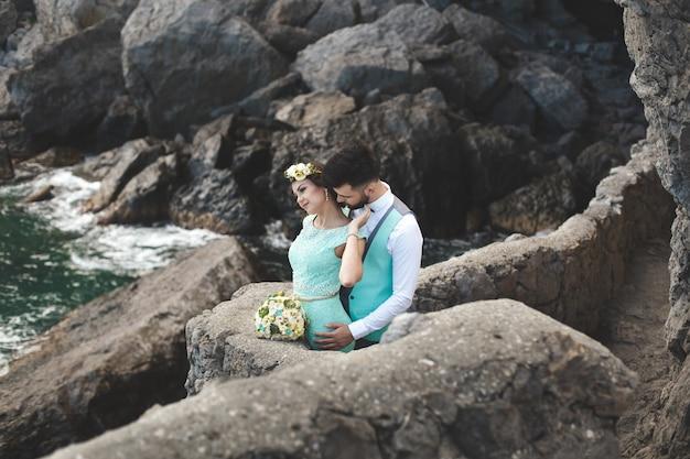 水の近くの山の自然の新郎新婦。スーツとドレスの色はティファニー。キスとハグ。
