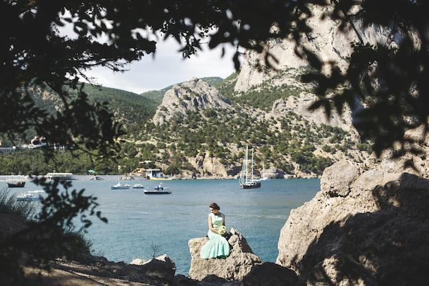 물 근처 산에서 자연에 신부와 신랑. 수트 및 드레스 색상 티파니. 돌 위에 앉아.