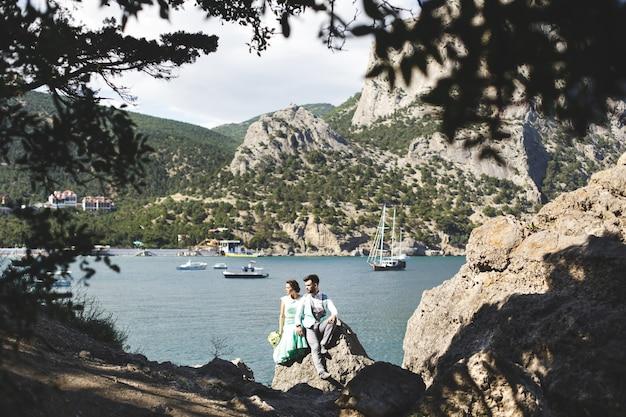 水の近くの山の自然の新郎新婦。スーツとドレスの色はティファニー。石の上に座っています。