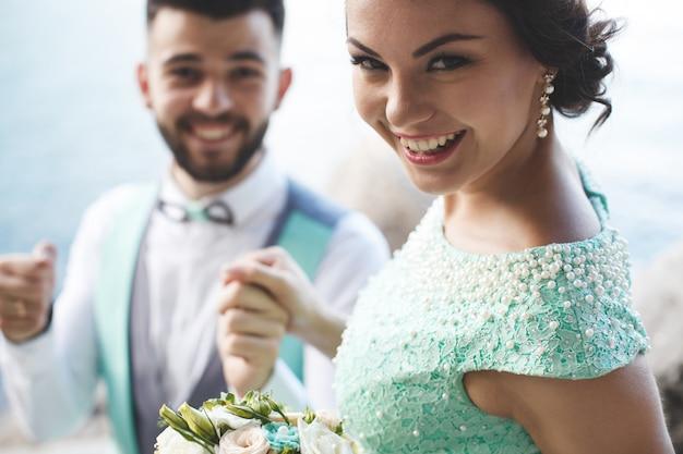 Жених и невеста на природе в горах у воды. костюм и платье цвета тиффани. жених смотрит вдаль.